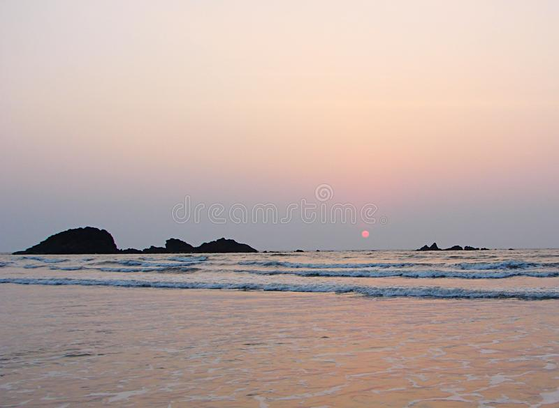 Rode Zon die bij Horizon over Overzees in Muzhappilangad aandrijving-in Strand, Kannur, Karala, India plaatsen - Natuurlijke Acht royalty-vrije stock fotografie