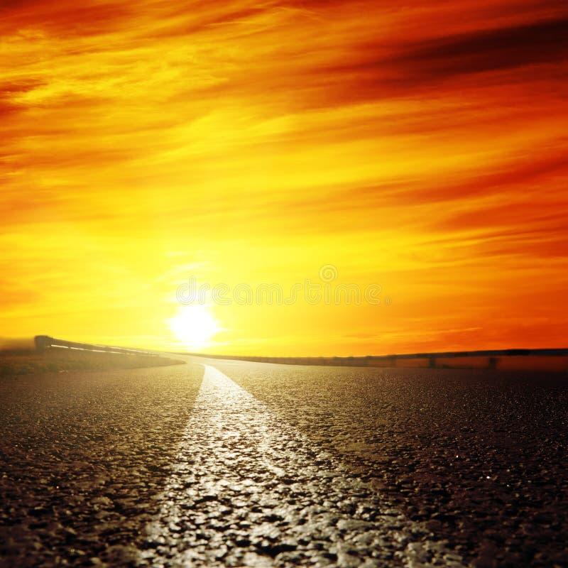 Rode zonsondergang en asfaltweg stock foto's
