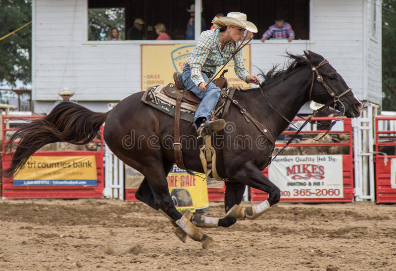 Rodeo Racer. A cowgirl clears a barrel and sprints home during a barrel racing event. The rodeo in Cottonwood, California is a popular event on Mother's Day stock photo