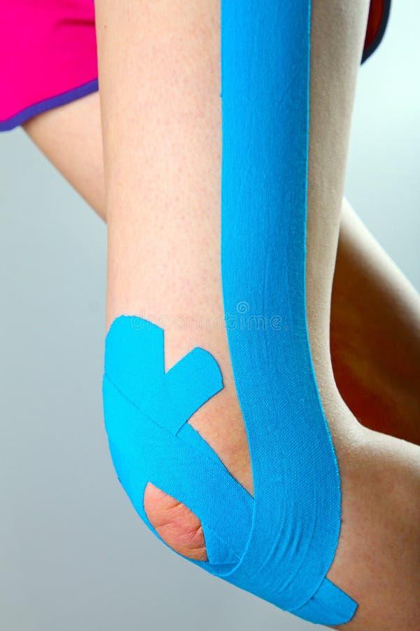 Rodilla con la cinta azul del kinesio imagen de archivo