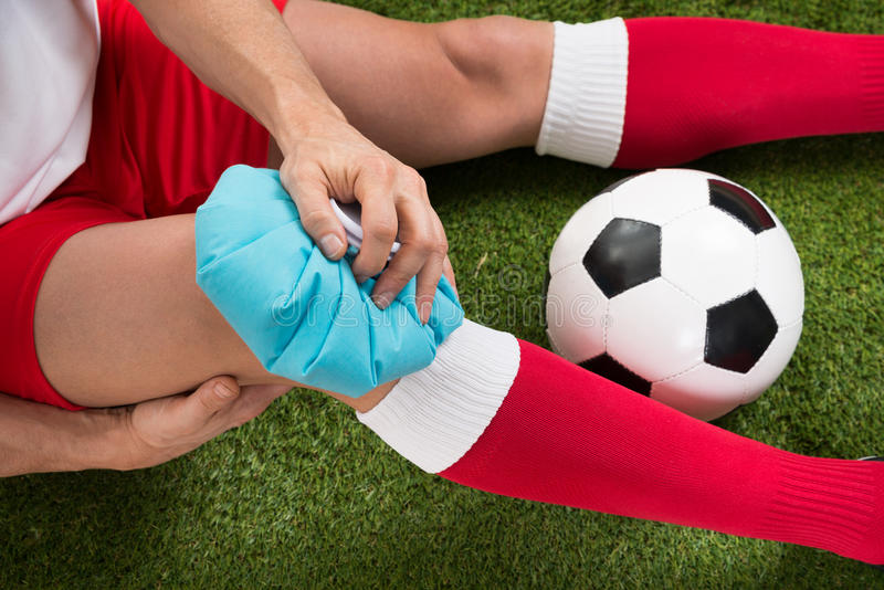 Rodilla de la formación de hielo del jugador de fútbol con la bolsa de hielo fotos de archivo libres de regalías