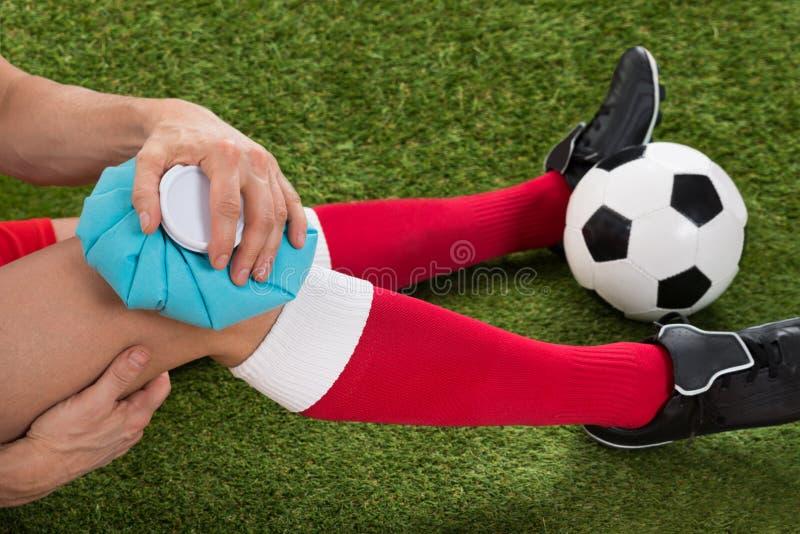 Rodilla de la formación de hielo del jugador de fútbol con la bolsa de hielo fotografía de archivo libre de regalías