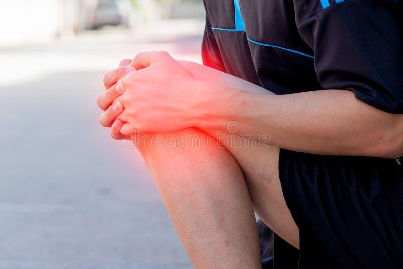 Rodilla dolorosa conmovedora del corredor Accidente de entrenamiento del corredor del atleta Esguince corriente de la rodilla del imagenes de archivo