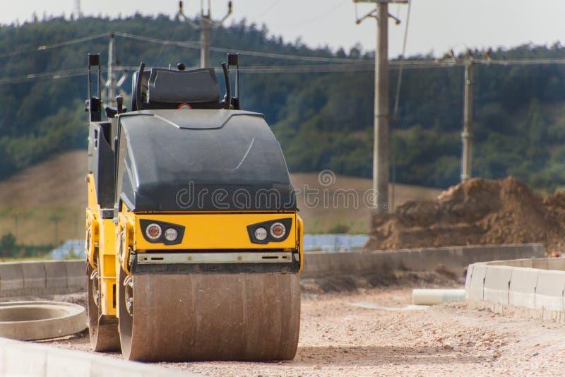 Rodillo de camino que trabaja en el nuevo sitio de la construcción de carreteras Máquina de la construcción en un emplazamiento d imagen de archivo libre de regalías