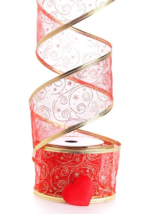 Rodillo de la cinta roja con el ajuste y el corazón del oro imagen de archivo libre de regalías