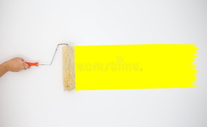 Rodillo de mano del ` s del pintor a pintar las pinturas amarillas del color en la pared gris fotos de archivo libres de regalías