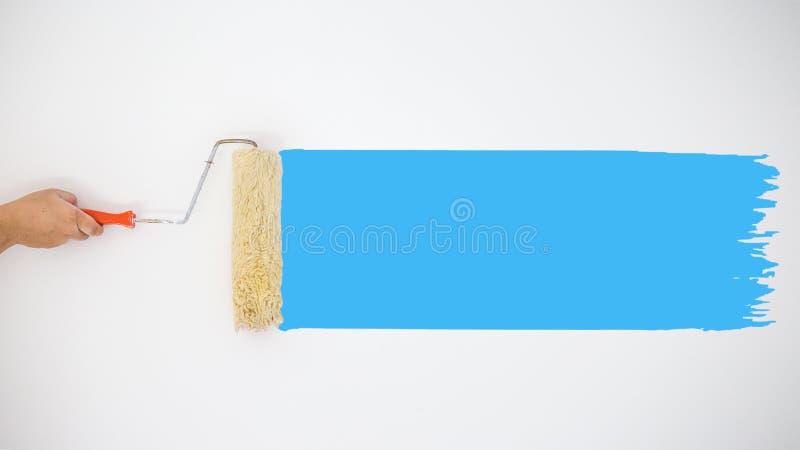 Rodillo de mano del ` s del pintor a pintar las pinturas azules del color en la pared gris imágenes de archivo libres de regalías