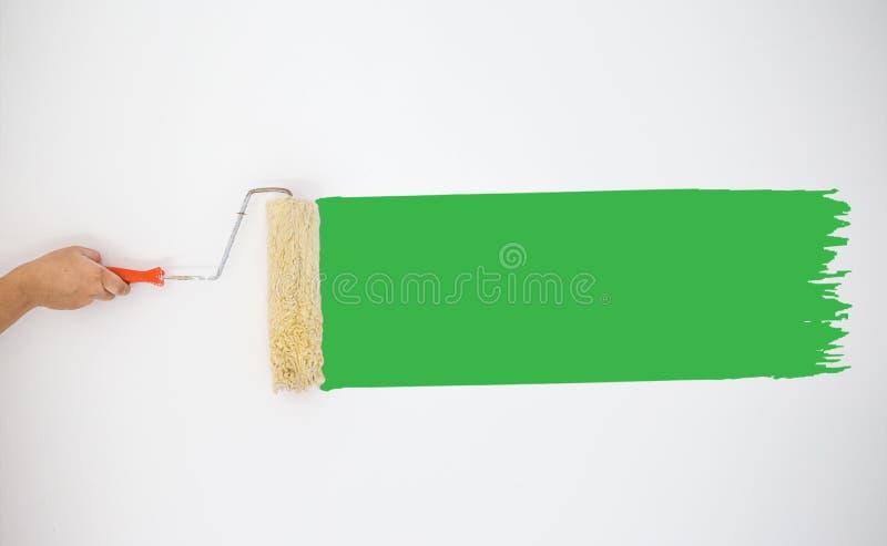 Rodillo de mano del ` s del pintor a pintar las pinturas del color verde en la pared gris fotos de archivo libres de regalías