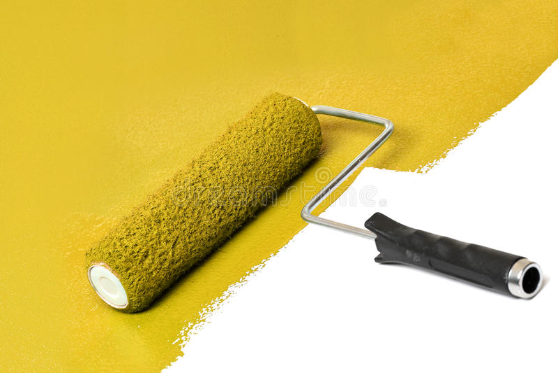 Rodillo de pintura amarillo sobre la superficie blanca foto de archivo libre de regalías