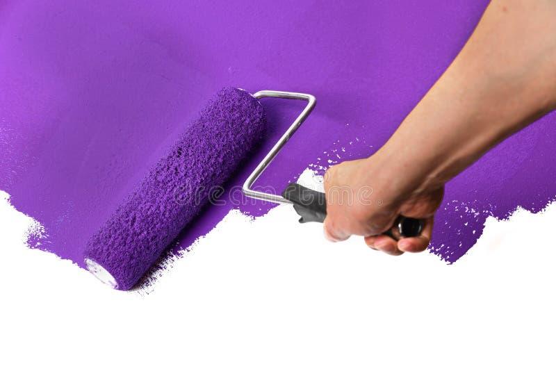 Rodillo de pintura con púrpura sobre la pared blanca fotografía de archivo libre de regalías