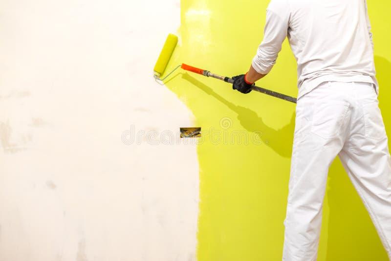 Rodillo de pintura del uso del pintor en la nueva pared restaurada imagen de archivo libre de regalías