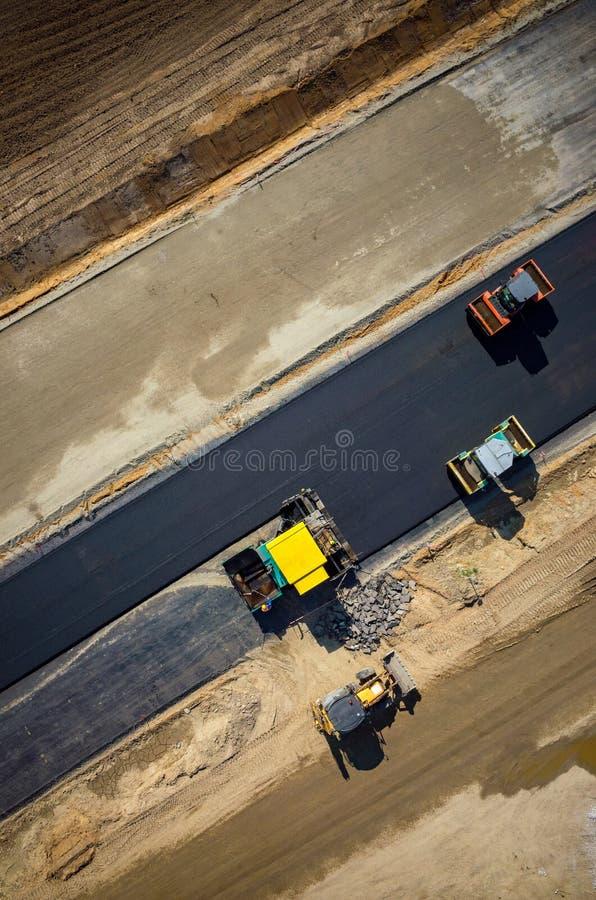Rodillos de camino que trabajan en la opinión aérea del emplazamiento de la obra imagen de archivo libre de regalías