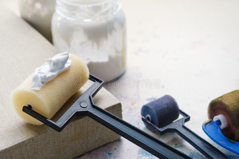 Rodillos del cepillo del artista para la capa de la lona y lona artística de lino para pintar Copie el espacio para el texto fotos de archivo