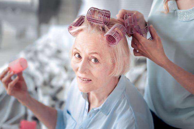 Rodillos del pelo de la mujer que llevan mayor agradable foto de archivo libre de regalías