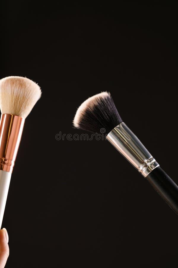 Rodnar kosmetiska borstar för smink med pulver explosion på svart bakgrund royaltyfri foto