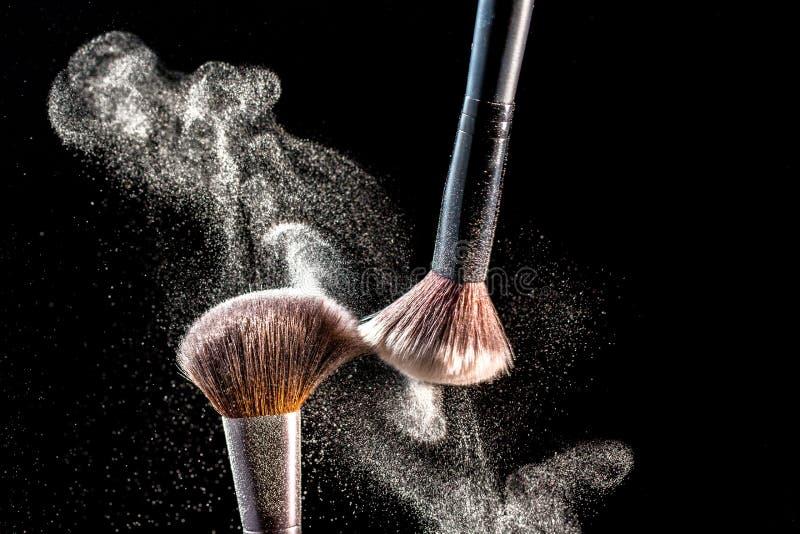 Rodnar kosmetiska borstar för smink med pulver explosion på svart bakgrund Hudomsorg eller modebegrepp royaltyfria foton