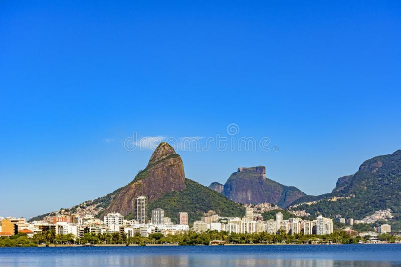 Rodrigo de Freitas lagoon skyline with Two Brothers hill, Gavea stone. And the surrounding buildings and calm waters stock photography