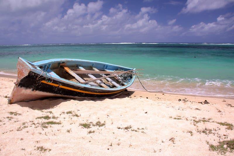 RODRIGUES-INSEL, MAURITIUS: Ein Fischerboot auf dem Strand und dem bunten Indischen Ozean lizenzfreie stockbilder