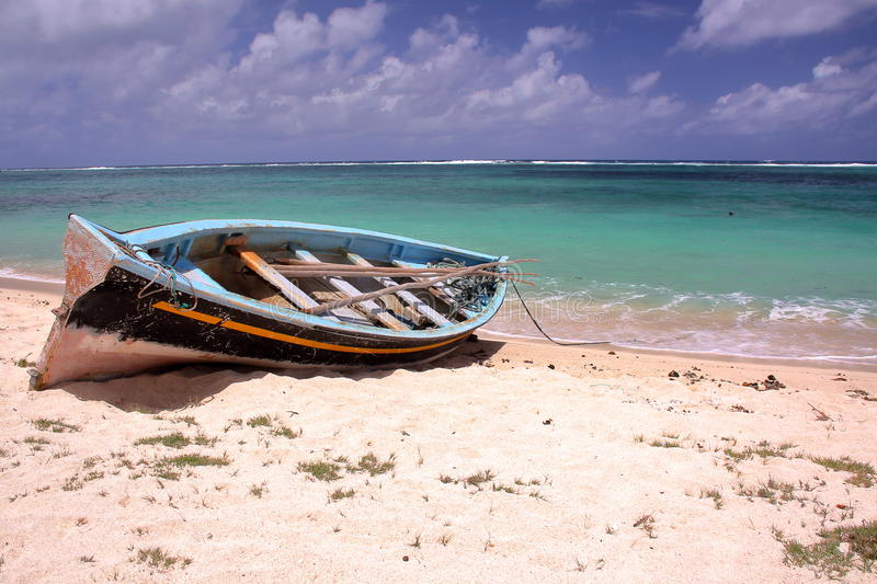RODRIGUES ISLAND, MAURITIUS: A fishing boat on the beach and the colorful Indian Ocean royalty free stock images