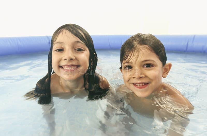 Rodzeństwa bawić się w plastikowym basenie patrzeje kamerę zdjęcie stock