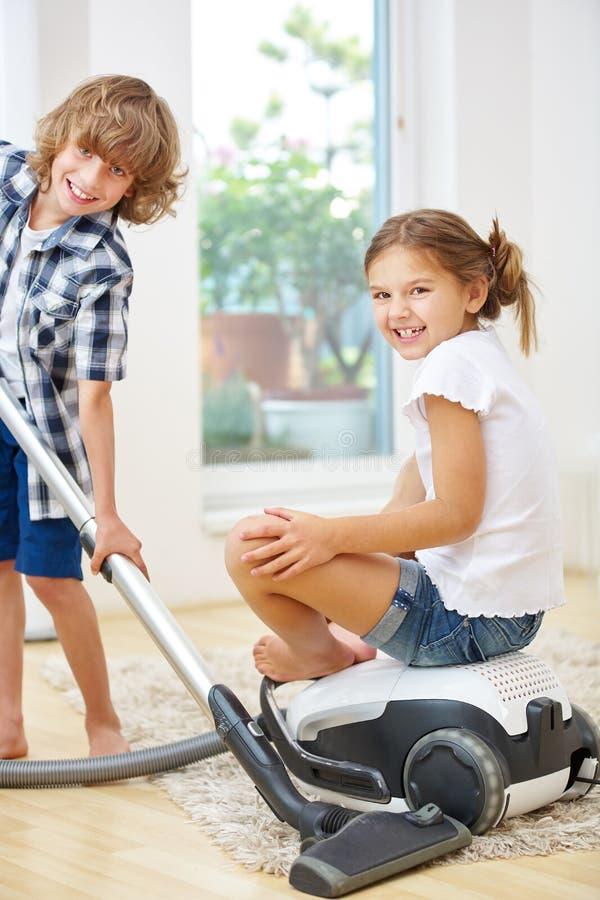 Rodzeństwa czyści do domu z próżniowym cleaner zdjęcie royalty free