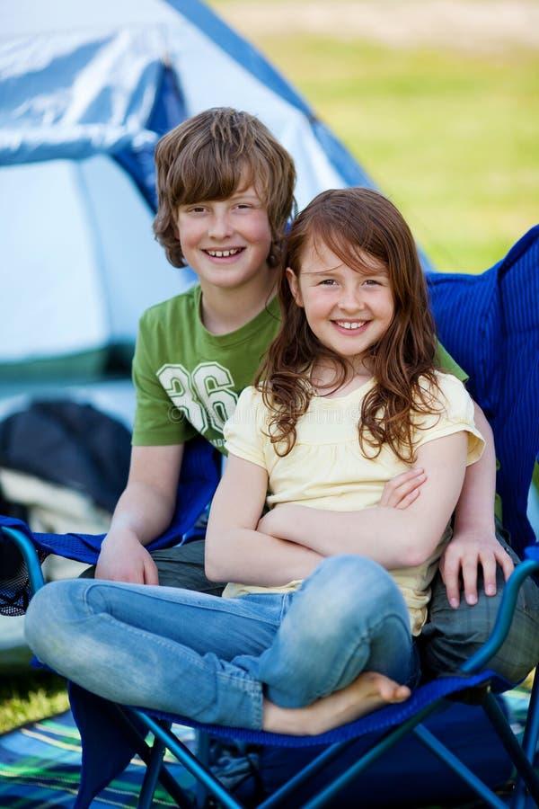 Rodzeństwa Siedzi Wpólnie Na krześle Z namiotem W tle zdjęcia stock