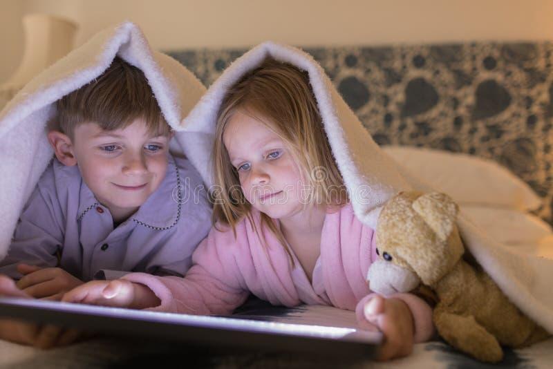 Rodzeństwa używa cyfrową pastylkę pod koc w sypialni zdjęcie stock