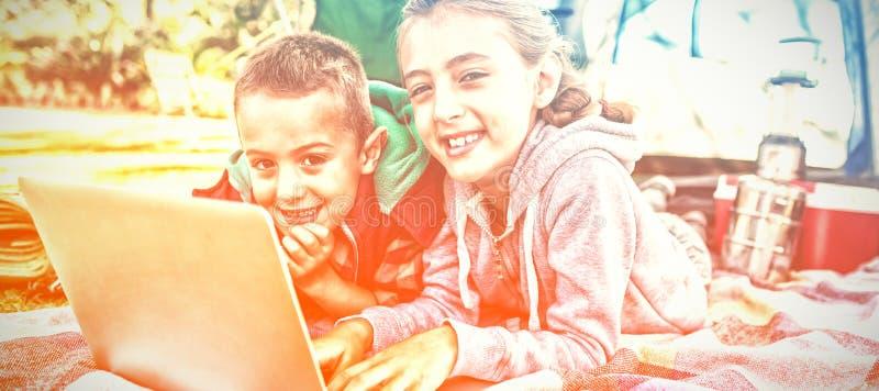 Rodzeństwa używa laptop na zewnątrz namiotu przy campsite fotografia royalty free