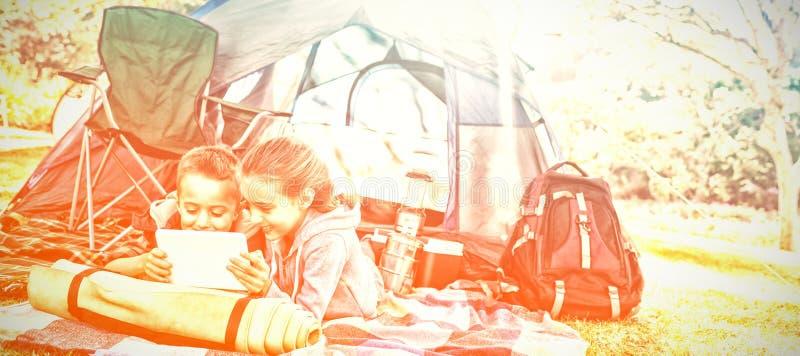Rodzeństwa używa laptop na zewnątrz namiotu przy campsite fotografia stock