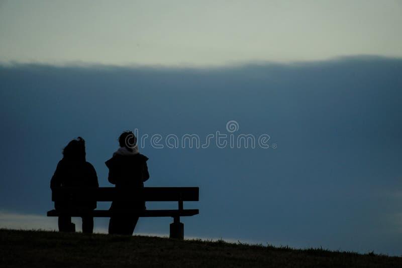 Rodzic i dziecko siedzieć w zmierzchu wzgórza ławka obrazy royalty free