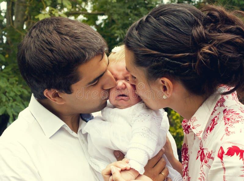 Rodzice całuje ich płaczu dziecka zdjęcia royalty free