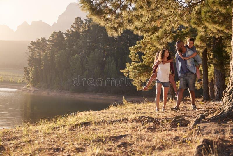 Rodzice Daje dzieci Piggyback przejażdżki Na spacerze jeziorem zdjęcie stock