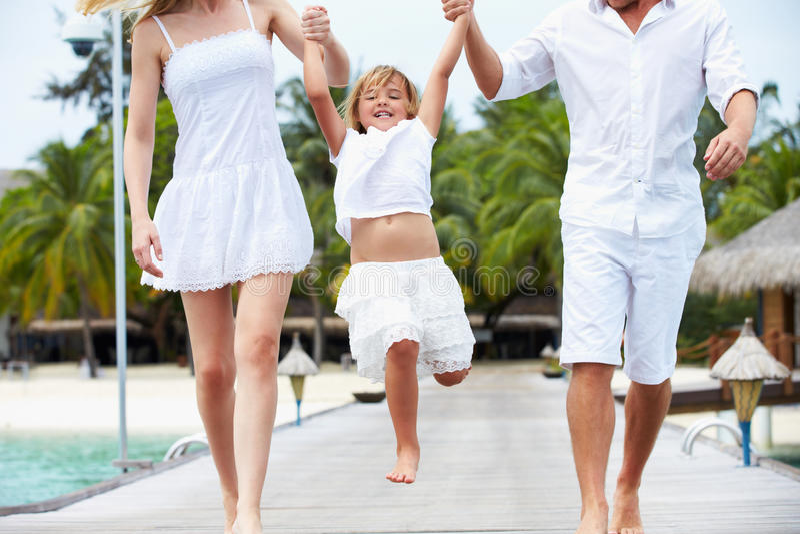 Rodzice Huśta się córki Gdy Chodzą Wzdłuż Drewnianego Jetty zdjęcie royalty free