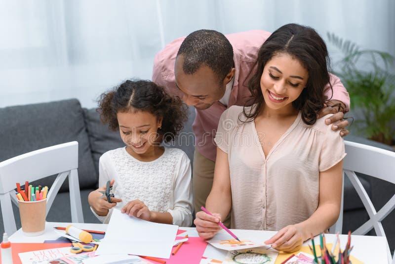 Rodzice i córka robi kartka z pozdrowieniami obrazy royalty free