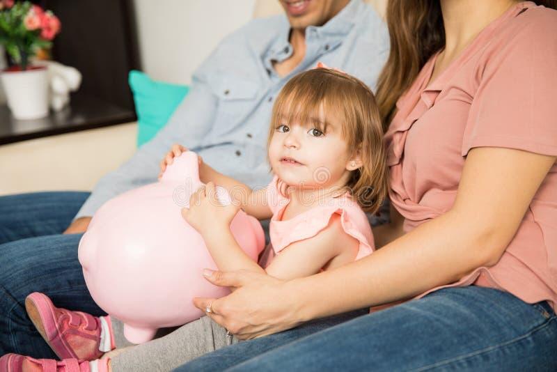 Rodzice i córka trzyma prosiątko banka obraz stock