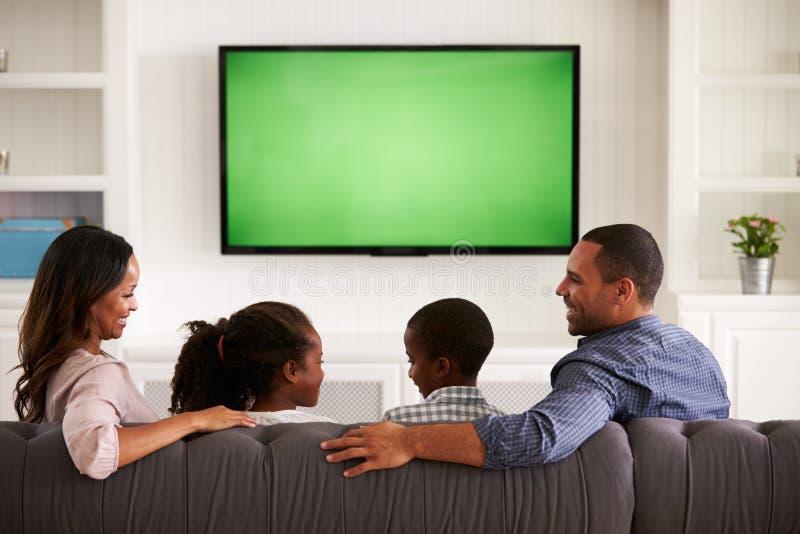 Rodzice i dzieci ogląda TV, patrzeje each inny zdjęcie royalty free
