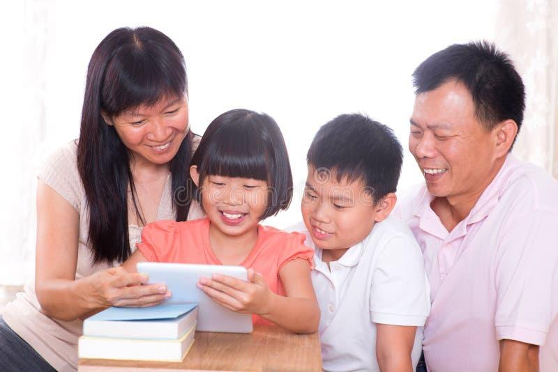 Rodzice i dzieci używa pastylka komputer osobisty wpólnie. obraz stock