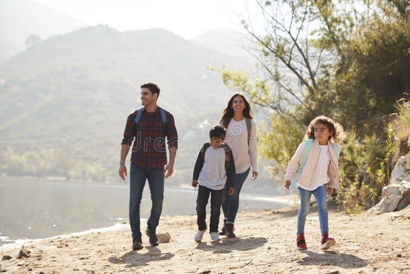 Rodzice i dzieci wycieczkuje halnym jeziorem w świetle słonecznym fotografia stock