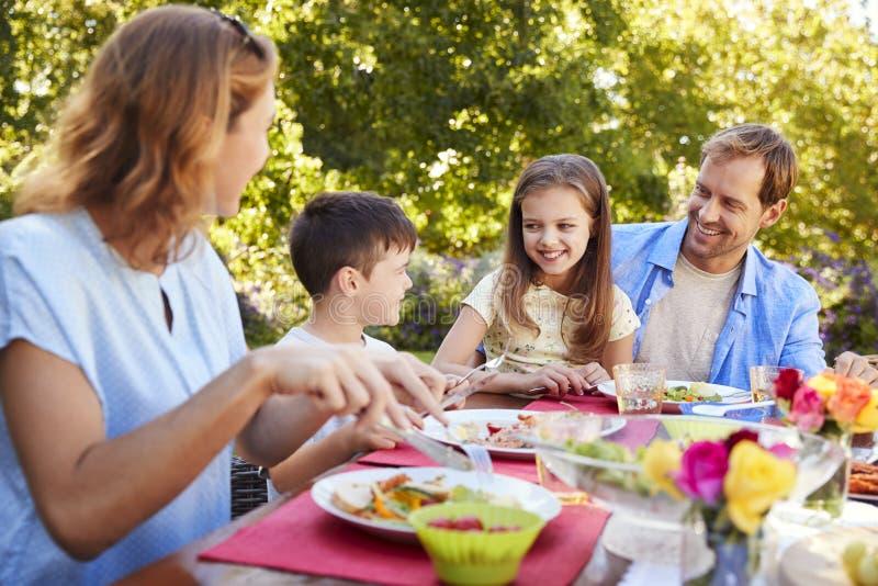Rodzice i dzieciaki ma lunch w ogródzie wpólnie zdjęcia royalty free