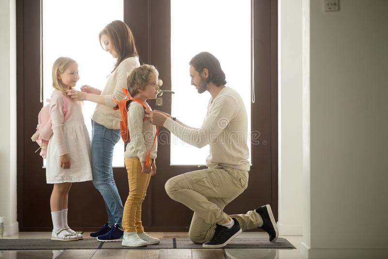Rodzice pomaga dzieci przygotowywać iść szkolna pozycja przy sala fotografia royalty free
