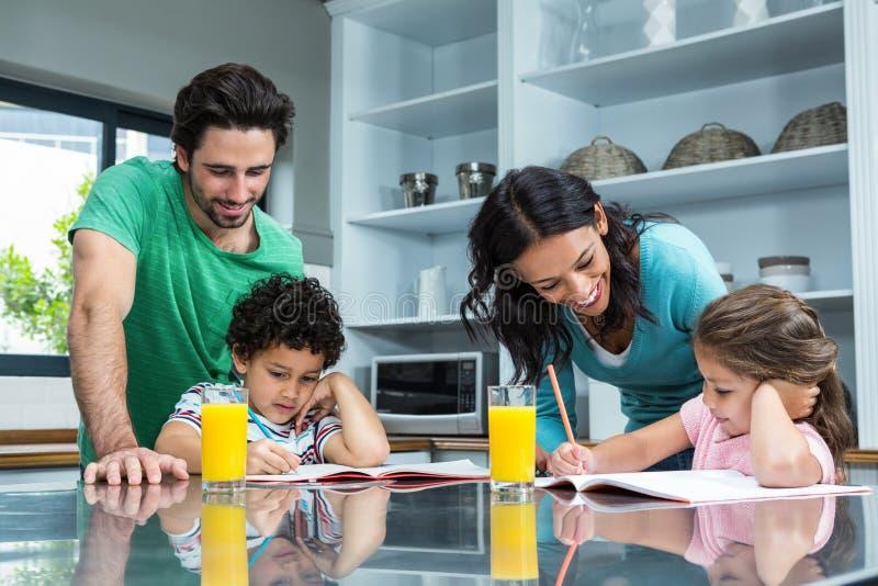 Rodzice pomaga ich dzieci robi pracie domowej obraz royalty free
