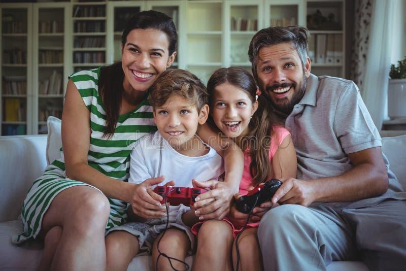 Rodzice siedzi na kanapie z ich dziećmi i bawić się wideo gry obraz royalty free