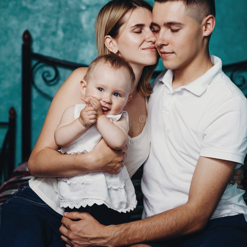 Rodzice siedzi wpólnie ściskający dziecko córki fotografia stock