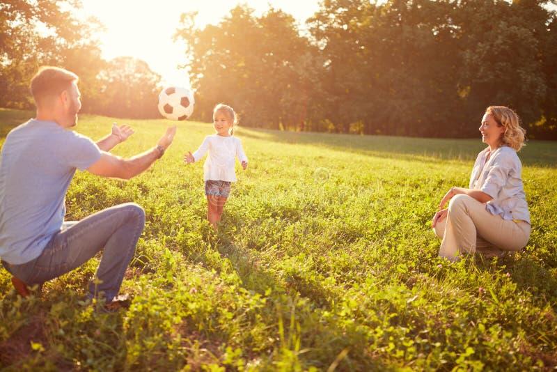 Rodzice z córką bawić się piłkę w parku zdjęcia royalty free