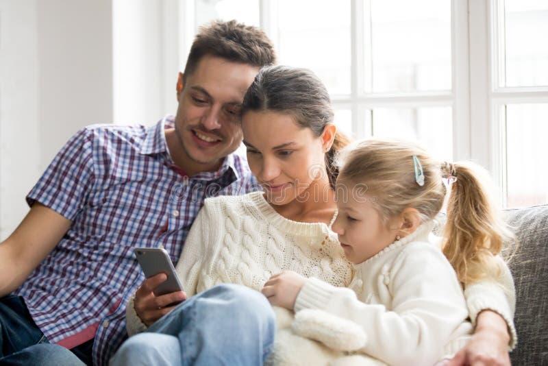 Rodzice z córki dopatrywania wideo na telefonie komórkowym w domu zdjęcia stock
