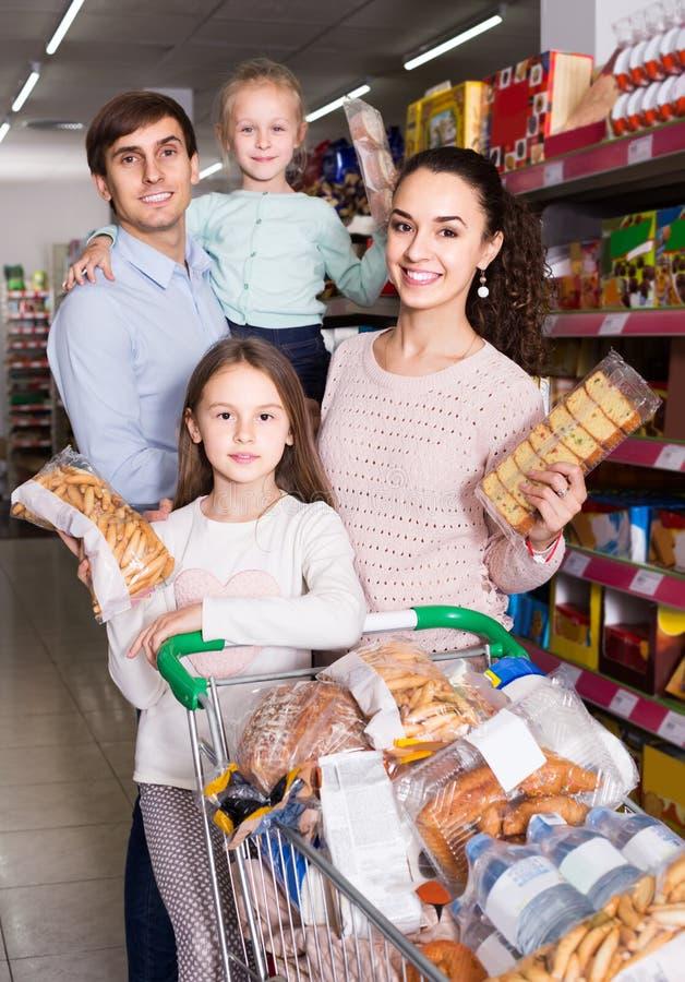Rodzice z dwa dzieciakami wybiera ciastka w sklepie obraz stock
