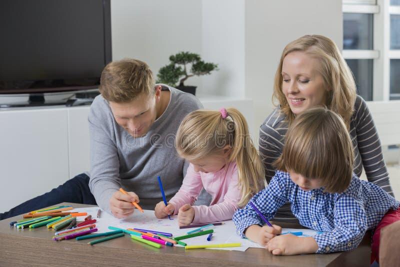 Rodzice z dziećmi rysunkowymi wpólnie w domu zdjęcia stock