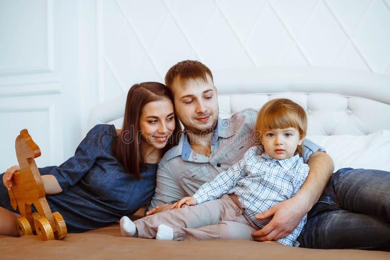 Rodzice z dzieckiem bawić się na łóżku z zabawkami zdjęcia royalty free