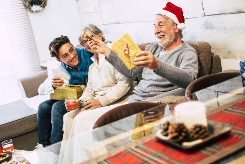 Rodzice z nastolatkami i dziadkami siedzieli w domu na kanapie rano świątecznego śmiechu i otwierając prezenty zdjęcia stock