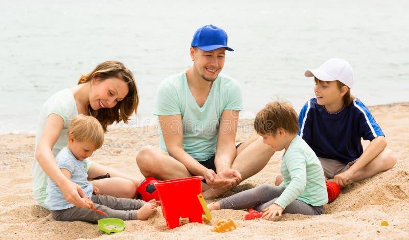 Rodzice z trzy dziećmi na plaży zdjęcia royalty free